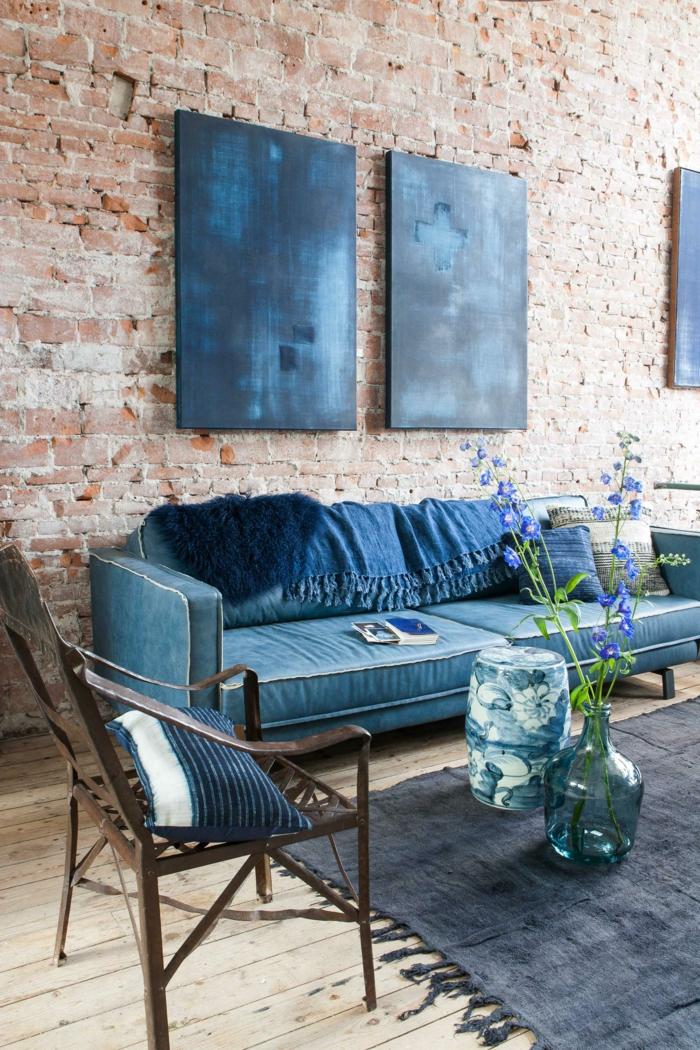 Zwei blaue Gemälde aufgehängt an Ziegelwand, großer Sessel und Teppich in blau, Stuhl aus Holz, außergewöhnliche Bilder