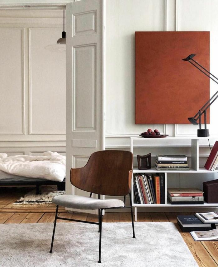 monochromes Gemälde in terrakotta Farbe, Wandbilder Wohnzimmer, kleines Regal mit Büchern, modischer Stuhl mit Lehne aus Holz