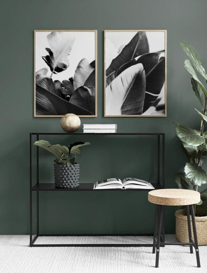 Dunkelgrüne mit zwei aufgehängte Bilder mit Naturmotiven, moderner schwarzer Kommode, große Wandbilder
