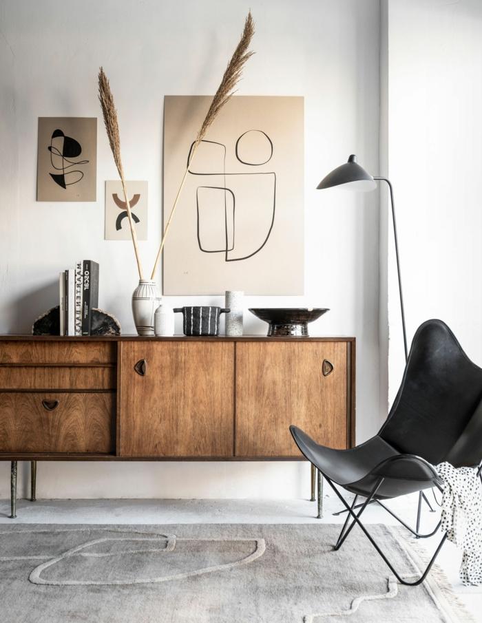 Moderne Inneneinrichtung mit Kommode aus Holz, Linienzeichnungen moderne Bilder, schwarzer Stuhl,