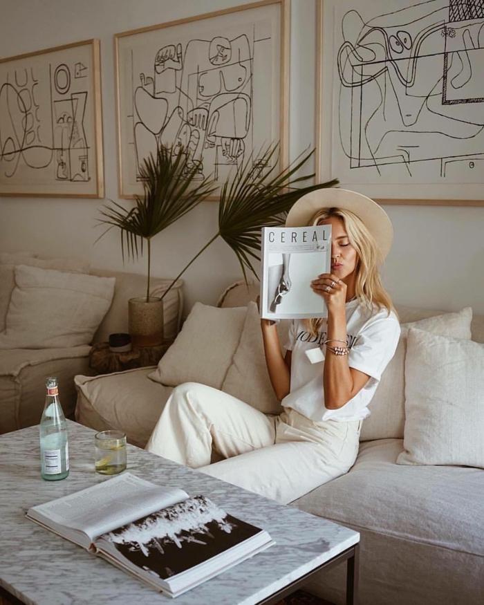 Drei große Linienzeichnungen, Bilder mit Rahmen, Blonde Frau in weißem Outfit liest Magazin auf weißem Sofa