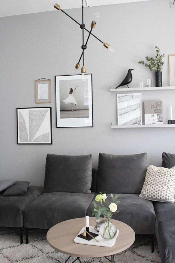 Couch in dunkelgrau, runder Tisch aus Holzmaterial, Bilder Wohnzimmer Ideen, drei aufgehängte Bilder,