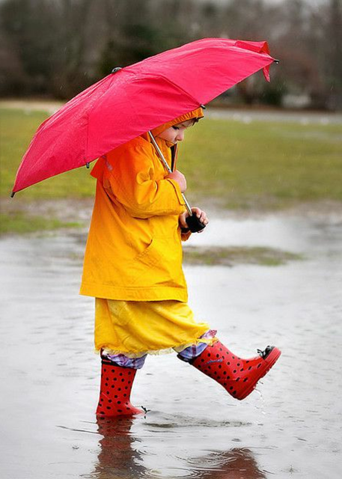 süßes-Kind-roter-Kinder-Regenschirm-im-Regen-laufen