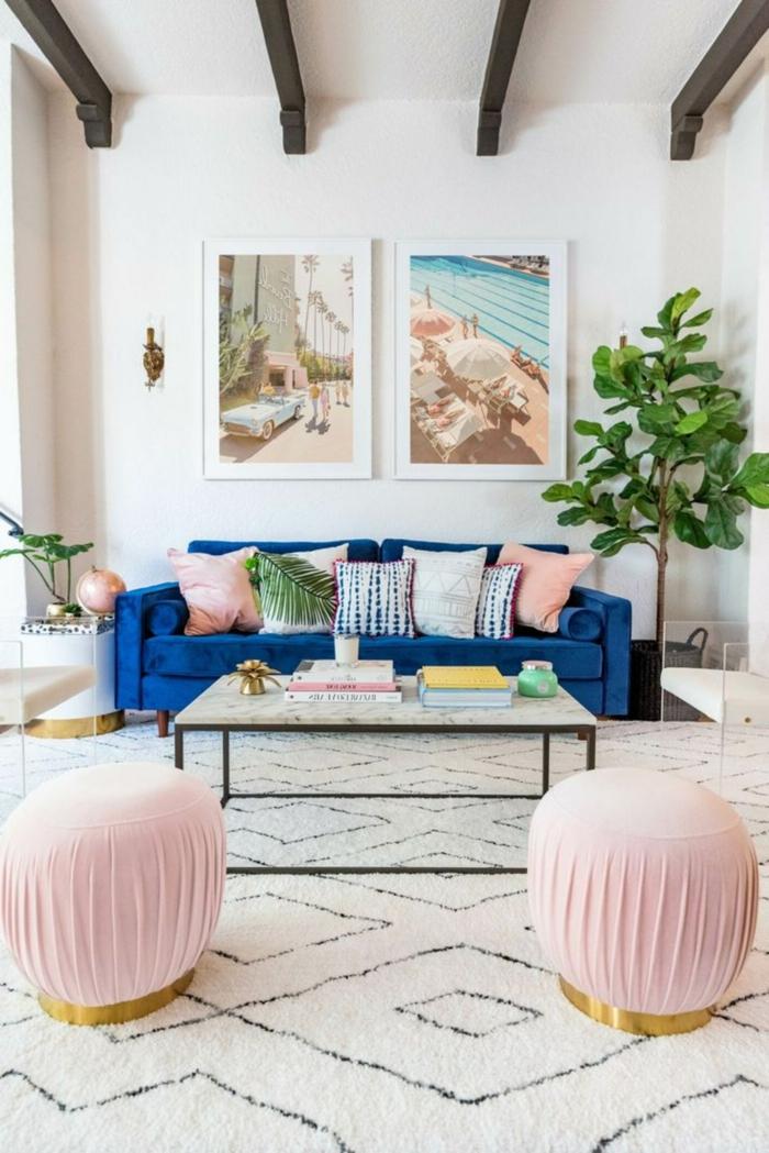 Couch in Blau mit vielen Kissen, rechteckiger Tisch, zwei kleine Hocker in pink, gerahmte Bilder für Wohnzimmer