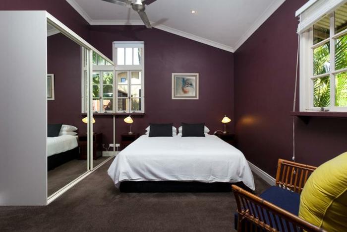 schöne-wandfarbe-aubergine-weißes-bett-im-schlafzimmer