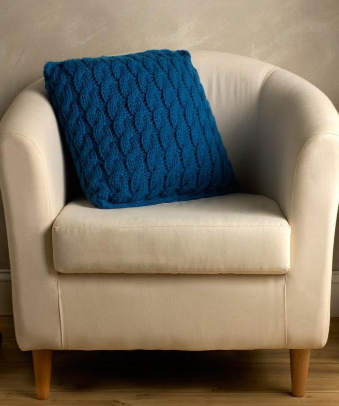 schöner-Sessel-beige-Farbe-Kissen-stricken-Modell-in-Blau-stricken-zopfmuster