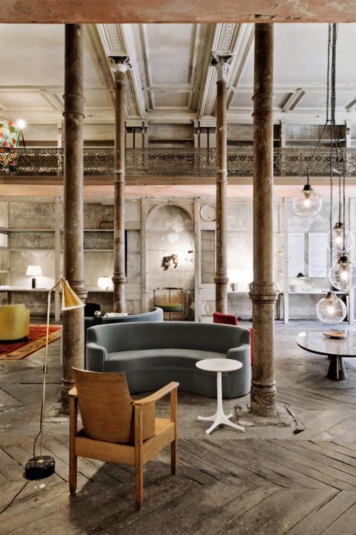 schlichte-industrielle-Einrichtung-kleines-halbrundes-Sofa-hölzerner-Stuhl-Stehlampe
