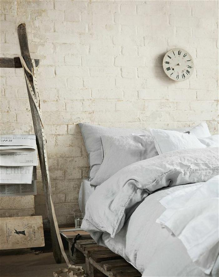 schlichtes-Schlafzimmer-Interieur-Europaletten-Bett-weiße-Bettwäsche-Wanduhr-klassisches-Modell-weiße-Ziegelwände