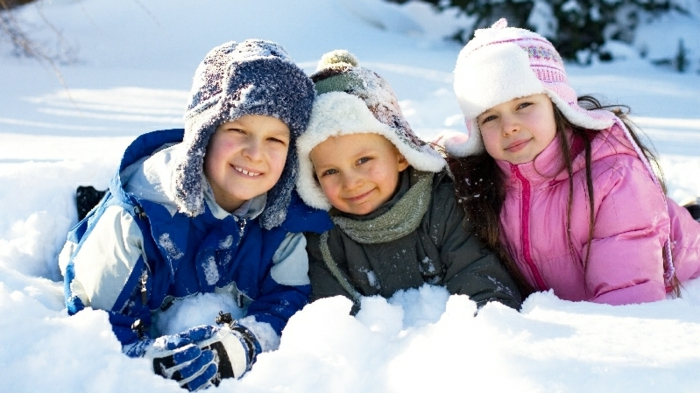 drei kinder haben spaß im schnee- sie werden schlitten fahren