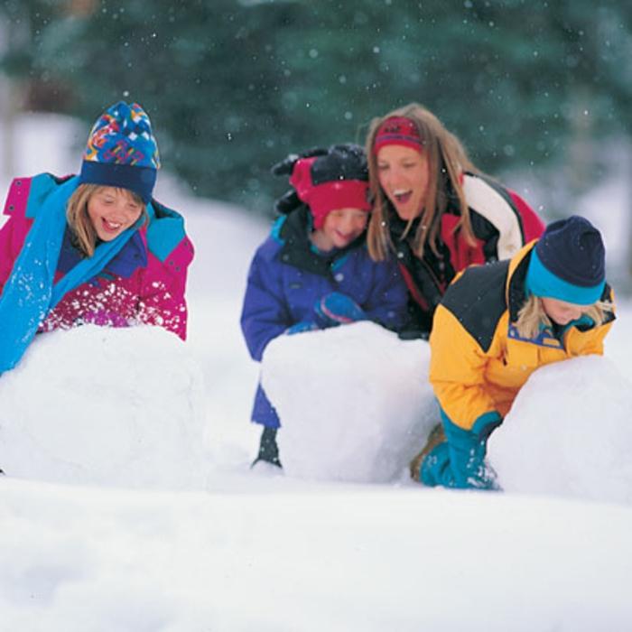 schneemann-bauen-drei-glückliche-kinder-im-schnee