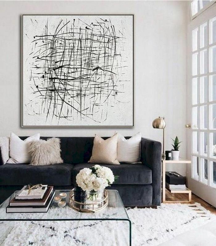 Bilder Wohnzimmer abstrakt, Couch in dunkler Farbe und helle Kissen, Tisch aus Glas mit Blumen obendrauf, artistisches Gemälde