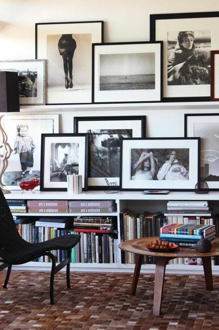 Fotografien von Personen, kleine Kommode mit Büchern, quadratischer Boden, runder Holztisch, Bilder mit Rahmen