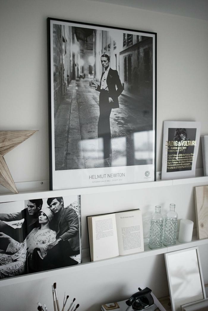 großes schwarz weißes Foto angelehnt an die Wand, aufgeschlagenes Buch, zwei Flaschen aus Glas, Schöne Wandbilder