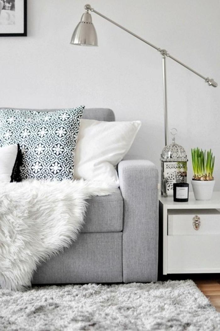 skandinavisches-Interieur-graues-Sofa-Pelz-Leselampe-aus-Metall-Bettbezug-mit-romantischem-Muster