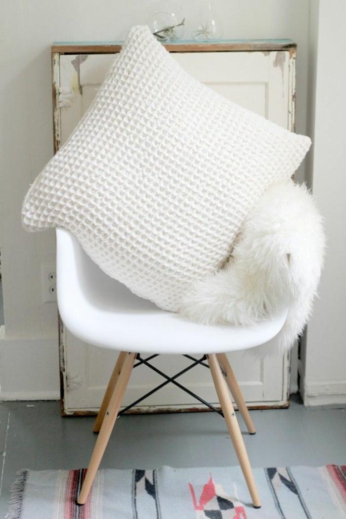 skandinavisches-Interieur-weißes-Pelz-Designer-Stuhl-schöner-stricken-Kissen-weiß