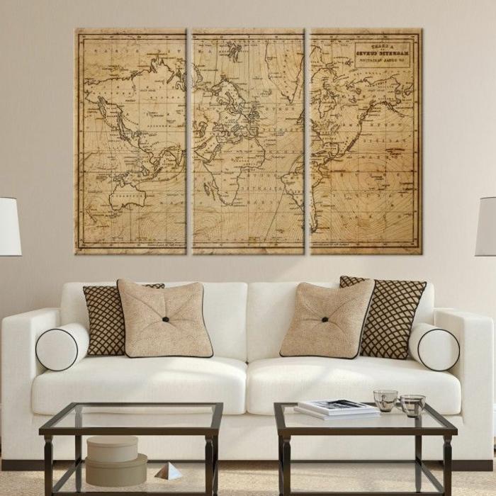 Außergewöhnliche Bilder, Couch in weiß mit beige Kissen, Bild von einer Weltkarte, zwei kleine Tische mit Glasplatten