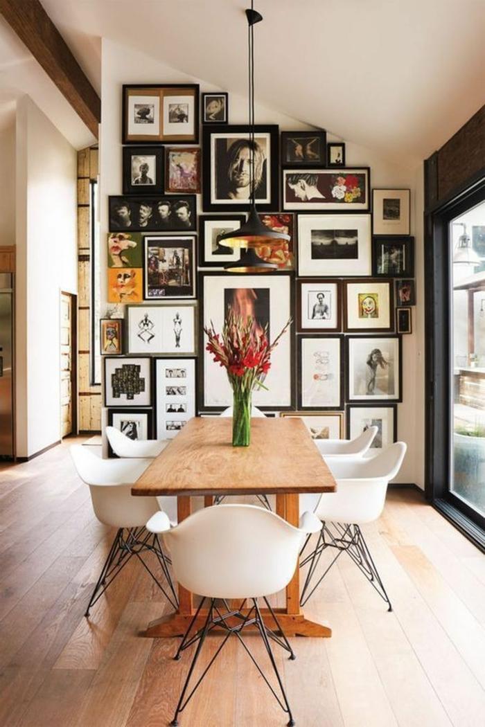 Wand mit Bildern und Zeichnungen bedeckt, bunte Bilder, gemalte Bilder, großer Esstisch aus Holz mit Blumen obendrauf