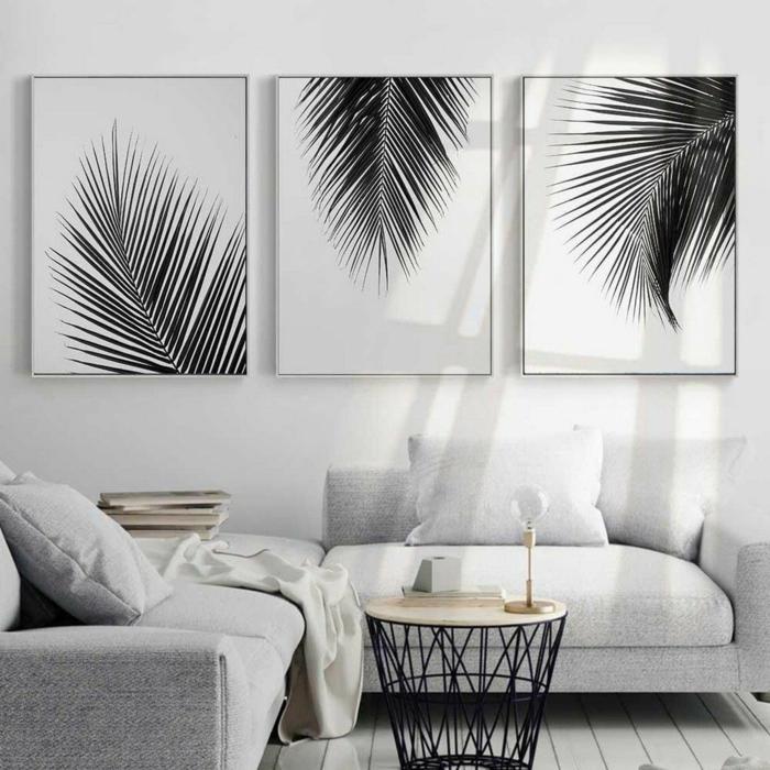 Drei Bilder von Palmenblätter, Inneneinrichtung von Wohnzimmer in heller Farbe, Korbtisch aus Metall, moderne Bilder
