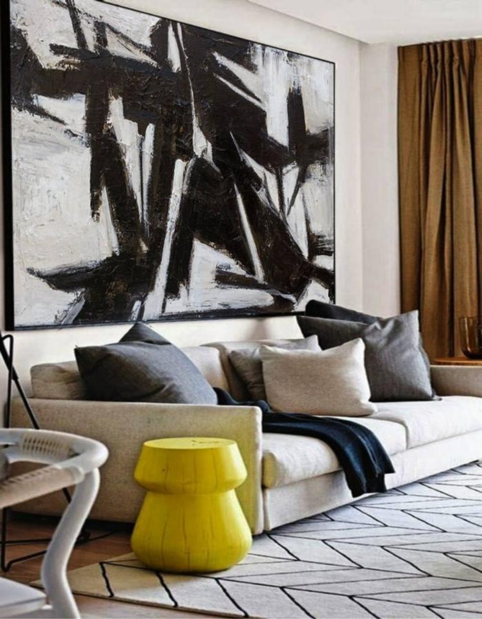 Wandbilder XXL, Couch in beige mit Kissen, kleiner Tisch in gelb, große Wandbilder in schwarz und weiß