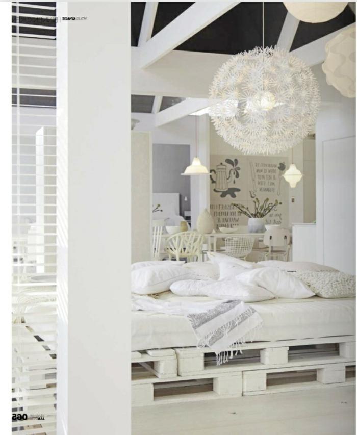 weißes-Schlafzimmer-Interieur-stilvoll-exquisit-bett-aus-europaletten-effektvoller-Kronleuchter
