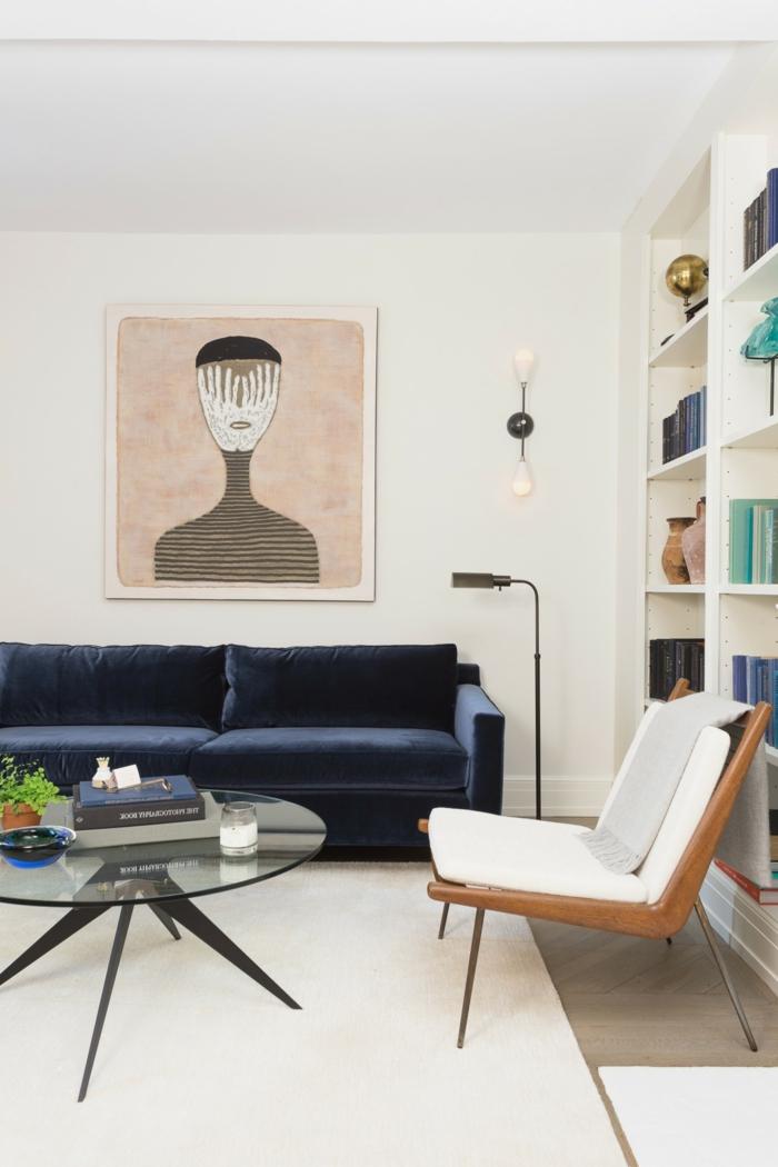 Großes Regal mit Büchern, Große Wandbilder von abstrakte Kunst, Bild von einem Gesicht, Sofa in blau, Teppich in weiß, runder Tisch