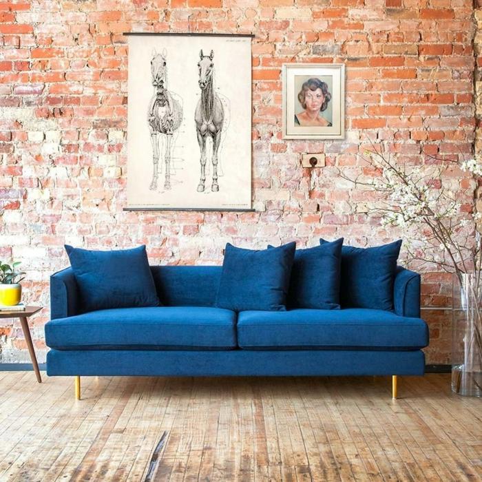 Bilder vom Pferd und einer Person aufgehängt an Ziegelwand, Couch in grell blau, Bilder Wohnzimmer Ideen