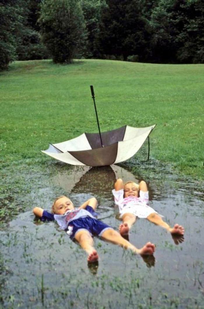 zwei-Kinder-im-Wasser-Regenschirm-Kinder-schwarz-weißes-Muster