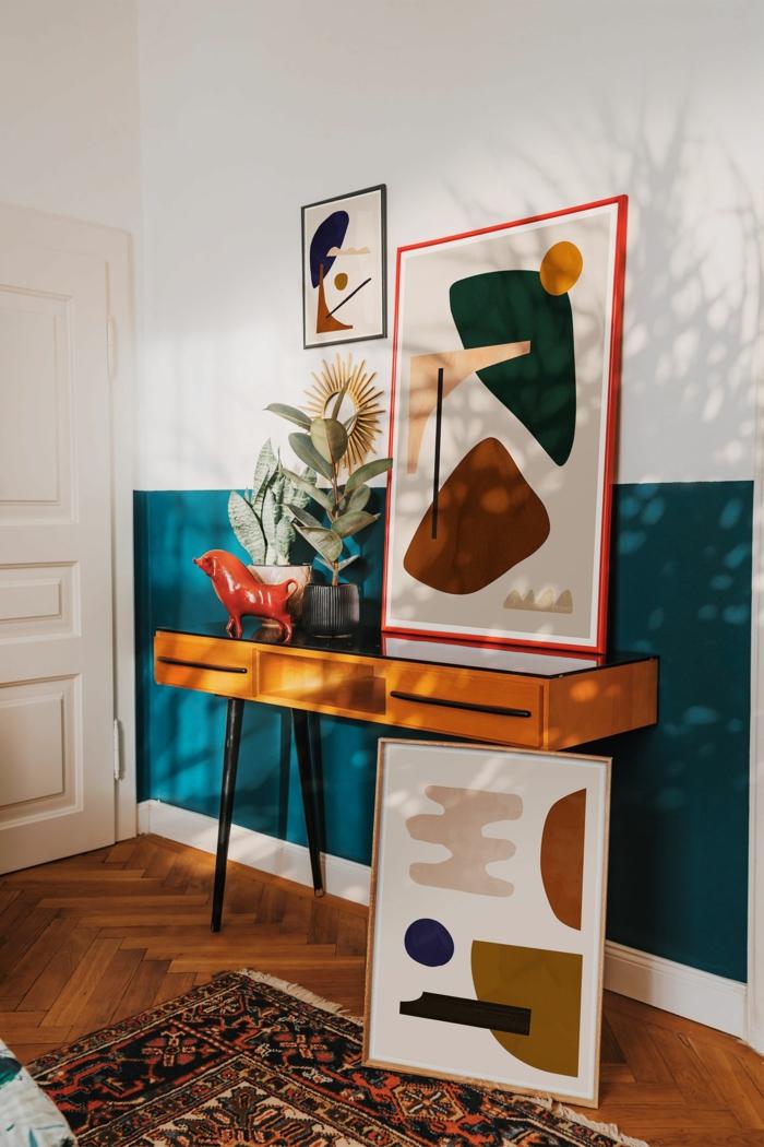 Drei abstrakte Bilder angelehnt an die Wand, Weiße und Blaue Wand, bunter Teppich, schöne Wandbilder