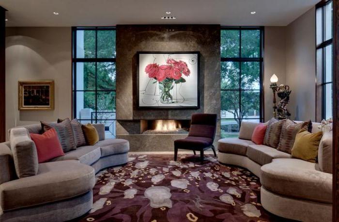 zwei-halbrunde-Sofas-Samt-extravaganter-Teppich-Sessel-weinrote-Farbe-schönes-Wandbild-Kamin
