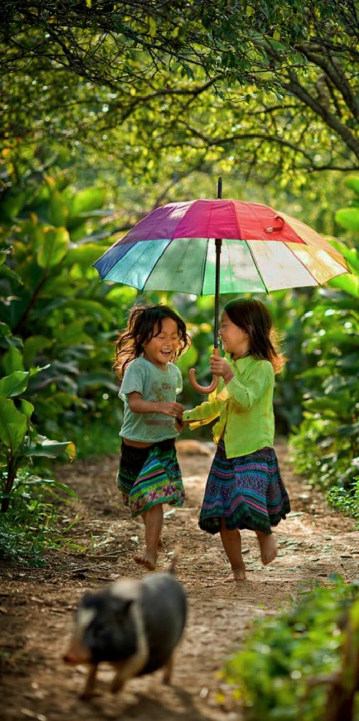 zwei-kleine-Mädchen-buntes-Modell-regenschirm-kinder