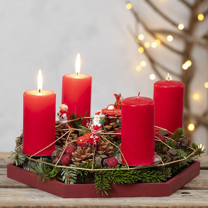 Adventskranz mit vier roten Kerzen, dekoriert mit Tannenzweigen, kleinen Weihnachtsfiguren und Zapfen