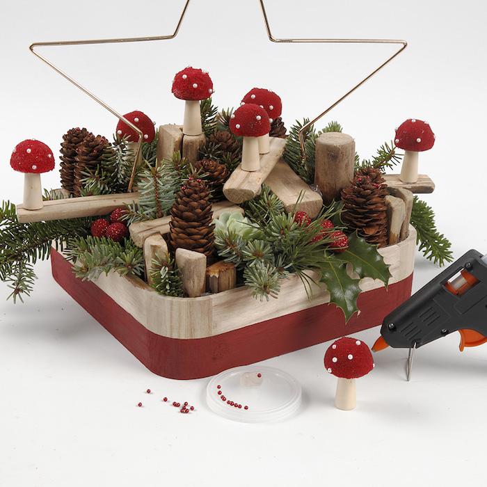 Holzständer mit Tannenzweigen, Tannenzapfen und kleinen Pilzen aus Holz dekorieren