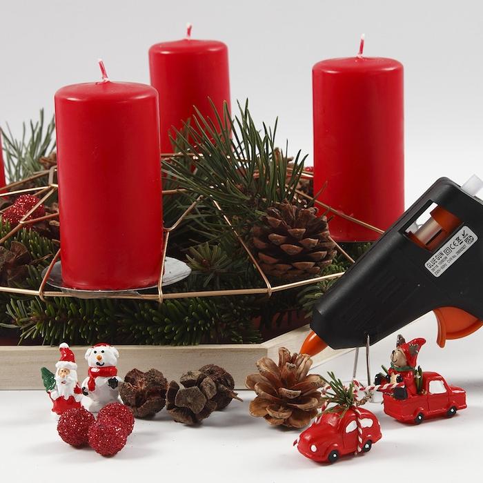 Adventskranz mit kleinen Weihnachtsfiguren und Tannenzapfen verzieren, vier rote Kerzen