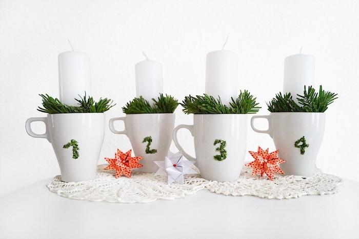 Alternative zum klassischen Adventskranz, weiße Kerzen in Tassen stecken, mit künstlichen Tannenzweigen verzieren, Nummer aus Nadeln