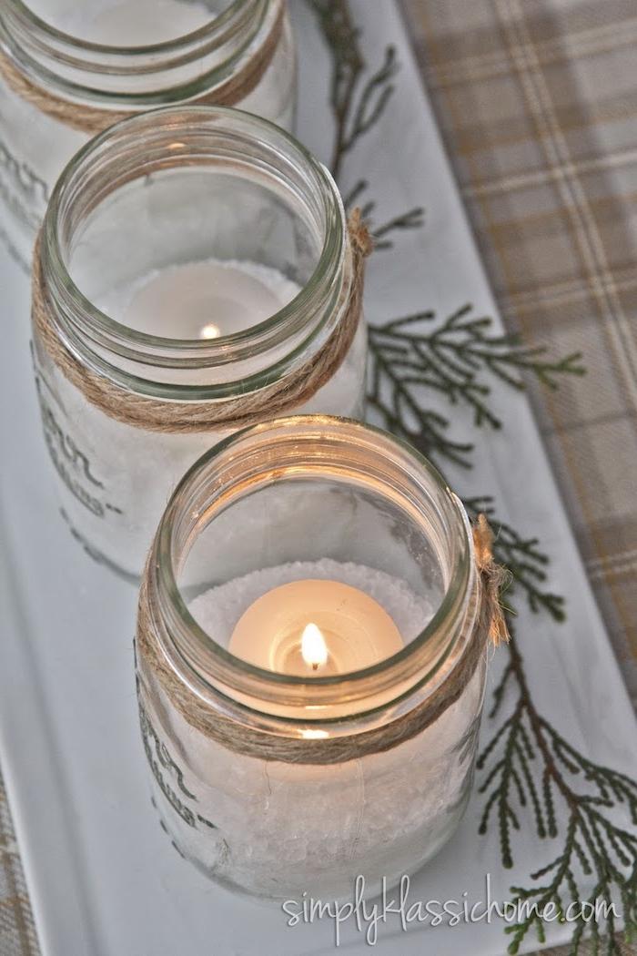 Weiße Kerzen in Einmachgläsern voll mit künstlichem Schnee, Adventskranz Idee zum Selbermachen