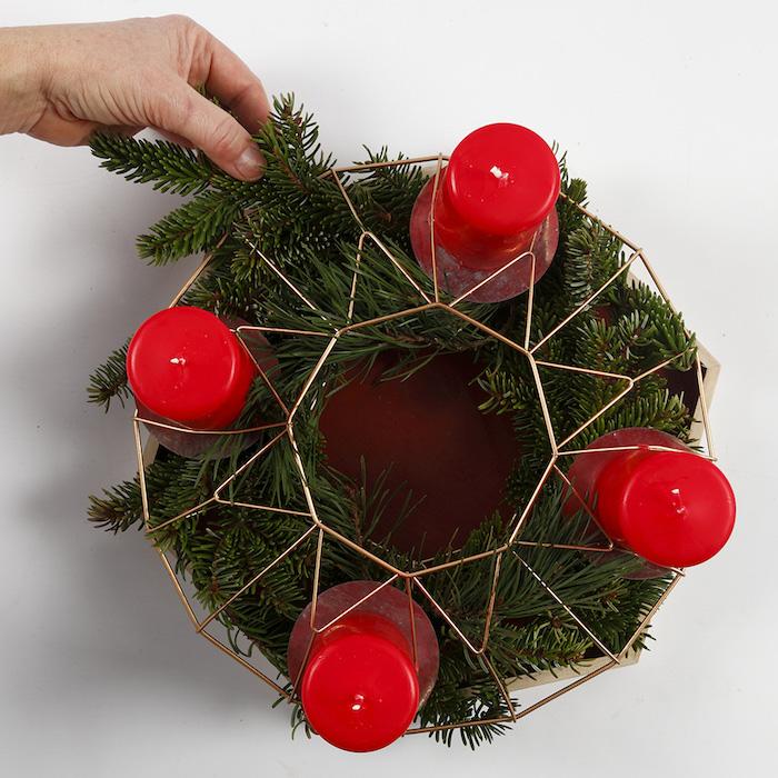 Adventskranz mit frischen Tannenzweigen, vier rote Kerzen stecken, Adventszeit Deko