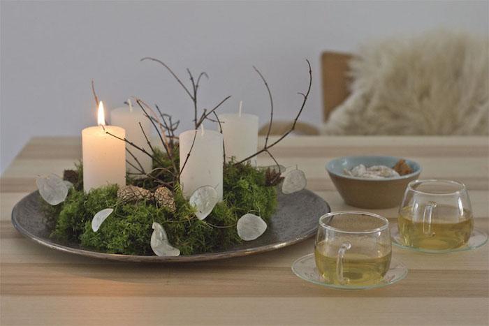 DIY Adventskranz mit weißen Kerzen auf großem Teller, zwei Tassen Tee, kleine Schüssel mit Plätzchen