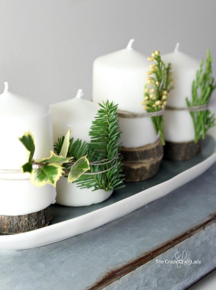 Adventskranz einfach zum Selbermachen, vier Kerzen mit Tannenzweigen und Blättern von Grünpflanzen verzieren