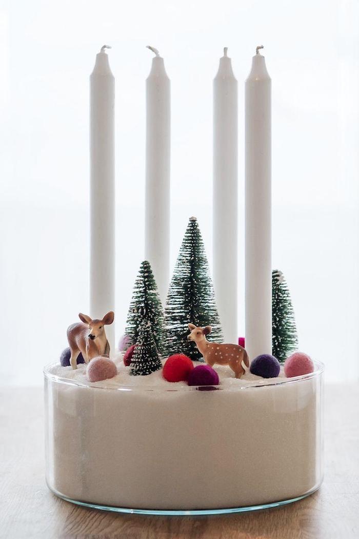 Adventskranz einfach und schnell zum Nachmachen, vier weiße Kerzen in Schüssel mit Sand, kleine Christbäumchen, Rehe und bunte Kugeln