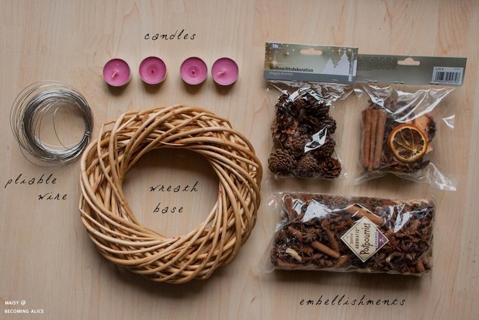 Materialien für DIY Adventskranz, vier Teelichter, dünner Draht, Tannenzapfen und getrocknete Früchte, Grund für den Kranz