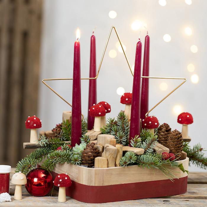 DIY Adventskranz Ideen, vier rote Kerzen in Holzständer, großer Stern aus Metall, Tannenzweige und Zapfen