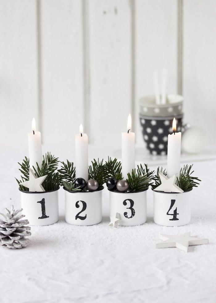 Alternative zum klassischen Adventskranz, weiße Kerzen in kleinen Tassen mit Nummern, verziert mit Tannenzweigen und kleinen Christbaumanhängern