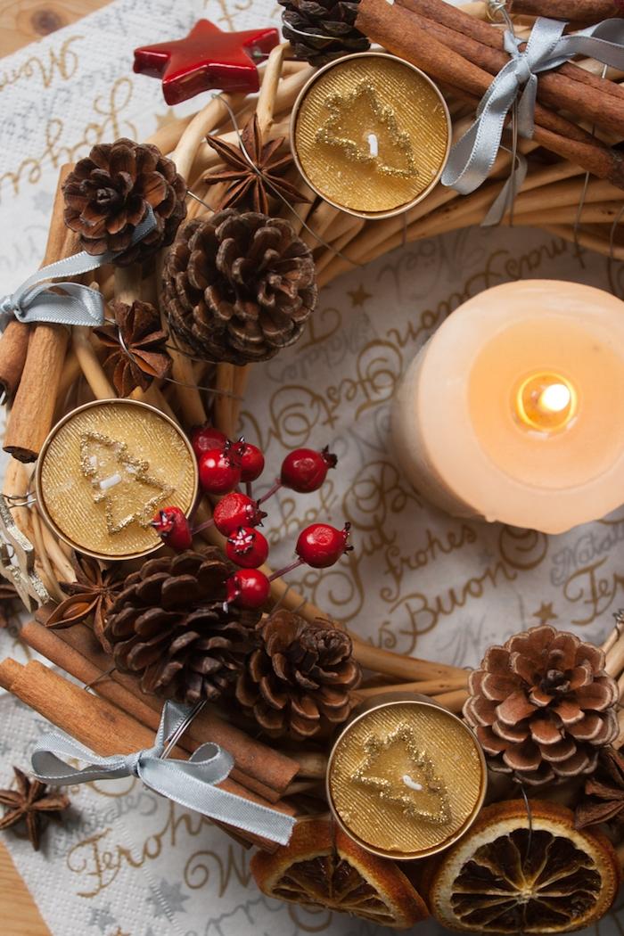 DIY Adventskranz mit goldenen Teelichtern, kleinen Tannenzapfen, getrockneten Orangenscheiben und Christbaumanhängern