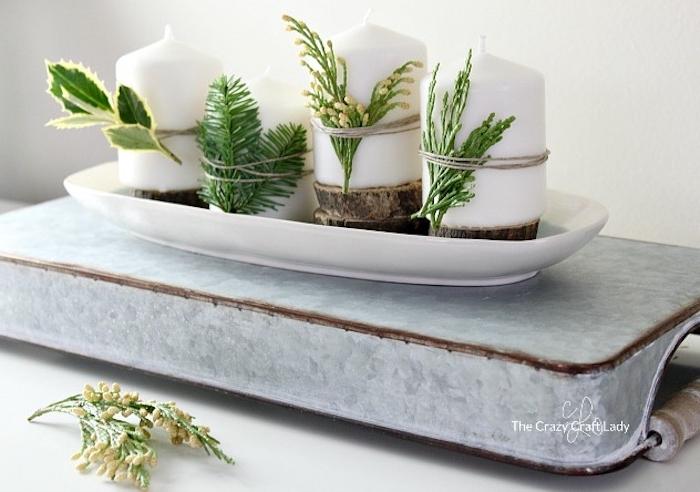 Idee für selbstgemachten Adventskranz, weiße Kerzen mit Tannenzweigen und Blättern von Grünpflanzen dekorieren