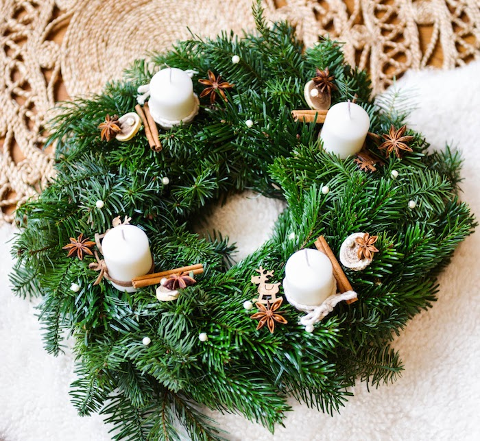 Adventskranz aus künstlichen Tannenzweigen, vier weiße Kerzen, dekoriert mit kleinen Holzfiguren und Zimt