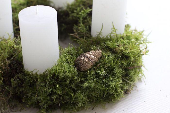 DIY Adventskranz aus Moos mit goldenen Tannenzapfen und großen weißen Kerzen