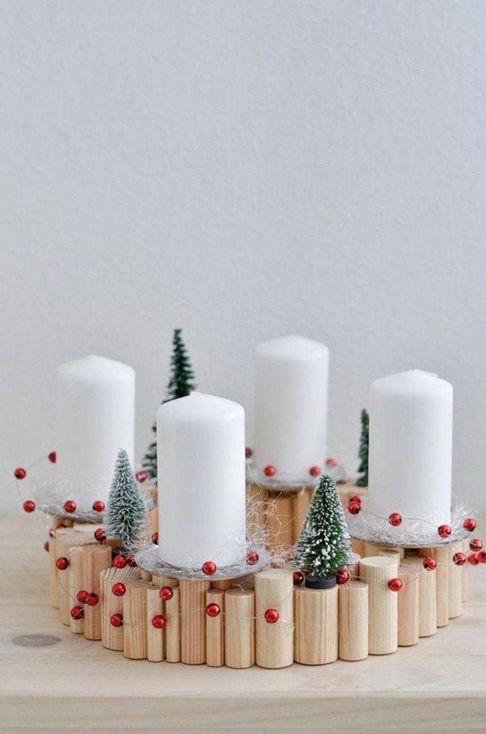 Adventskranz selber basteln, vier weiße Kerzen auf Ständer aus Holz, kleine Christbäumchen und rote Kugeln