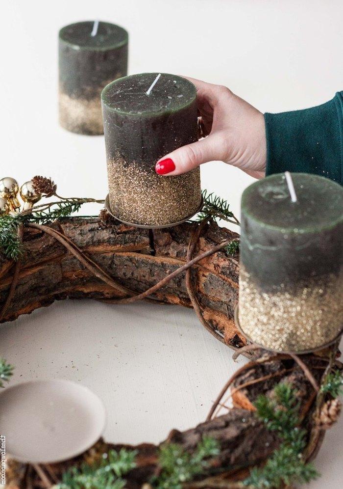 Große schwarze Kerzen mit goldenem Glitzer auf Adventskranz aus Baumrinde platzieren, mit Tannenzweigen und kleinen Christbaumkugeln verzieren