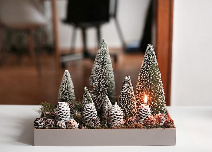 Kreative Idee für selbstgemachten Adventskranz, vier Kerzen in Form von Tannenzapfen, kleine Christbäumchen mit künstlichem Schnee