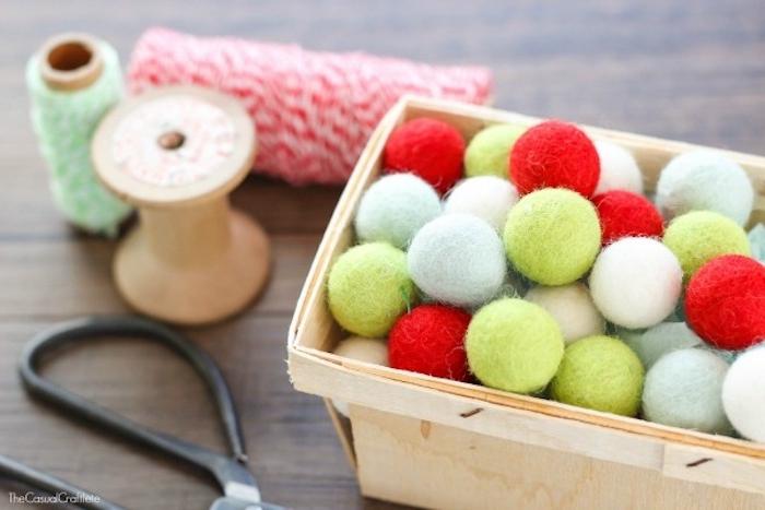 Materialien für DIY Weihnachtsschmuck, bunte kleine Kugeln aus Watte, Faden und Schere